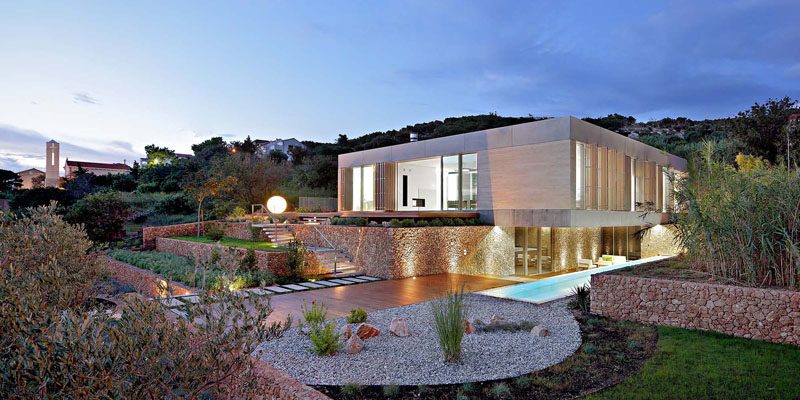 Architecture firm LOG-URBIS have designed a modern house on a sloped site on the island of Pag in Croatia, that has a terraced landscaped yard, a long swimming pool and water views. #ModernArchitecture #ModernHouse #LandscapedYard #SwimmingPool