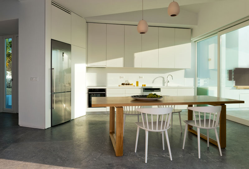 This modern and minimalist kitchen has white cabinets that blend into the walls, while a wood table with white chairs provides a place to eat. #WhiteKitchen #WoodDiningTable #ModernInteriorDesign