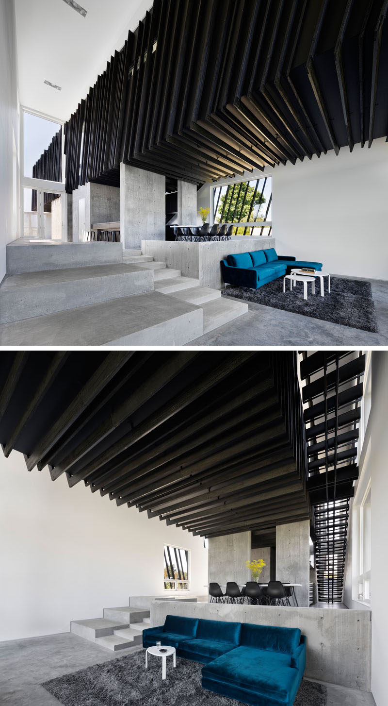 Stepping down from the dining room in this modern house is the living room. A pop of color has been added to the space in the form of a bright blue couch that looks out to the surrounding scenery through the large windows. #ModernLivingRoom #ConcreteFloor #ShouSugiBan #BlackCeiling #ModernHouse