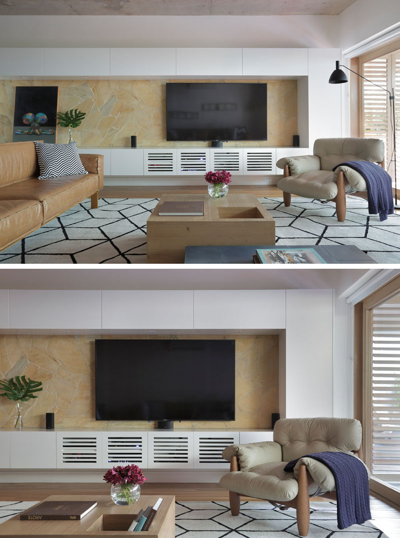 In this modern living room, a custom white cabinetry runs the length of the wall and acts as an entertainment unit. #EntertainmentUnit #Storage #LivingRoom #ModernInteriorDesign