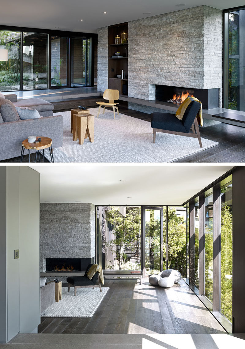 This modern living room is slightly stepped down from the hallway. A stone accent wall has a built-in wood bookcase and fireplace. Large floor-to-ceiling windows flood the room with natural light. #Fireplace #StoneWall #AccentWall #ModernLivingRoom #Windows