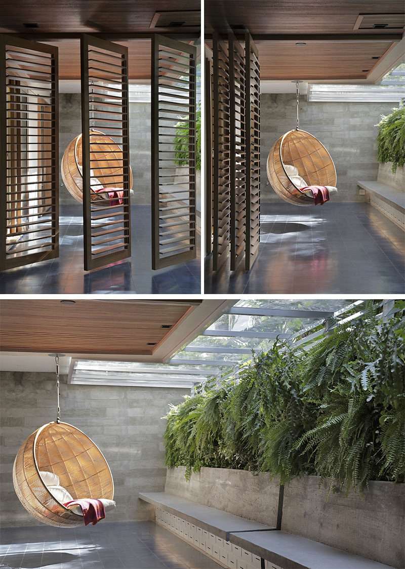 This modern outdoor space is separated into two areas, with wood louvre screens that can be pushed aside to open the space up or closed when privacy is required. The hanging chair is located off the master bedroom. #OutdoorSpace #HangingChair #LouvreShutters #SlidingShutters