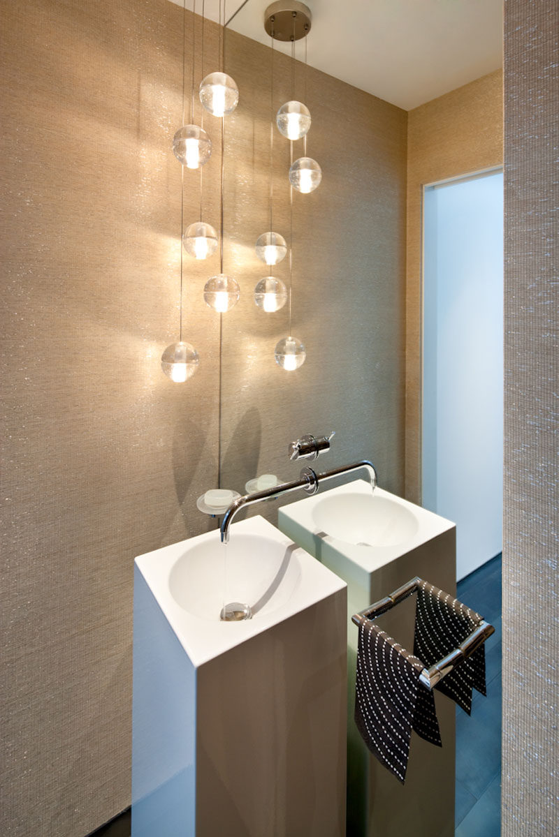In this modern powder room, an entire wall is filled with a mirror to make the small space feel larger. #PowderRoom #LargeMirror #InteriorDesign