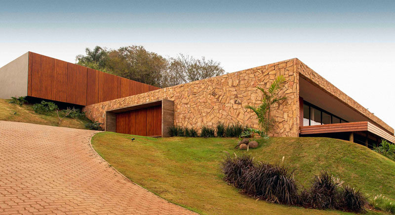 mf+arquitetos have designed Casa Das Pedras, a modern house in Franca, Brazil, that's been built using stone, wood and bricks. #ModernHouse #Wood #Stone #Architecture