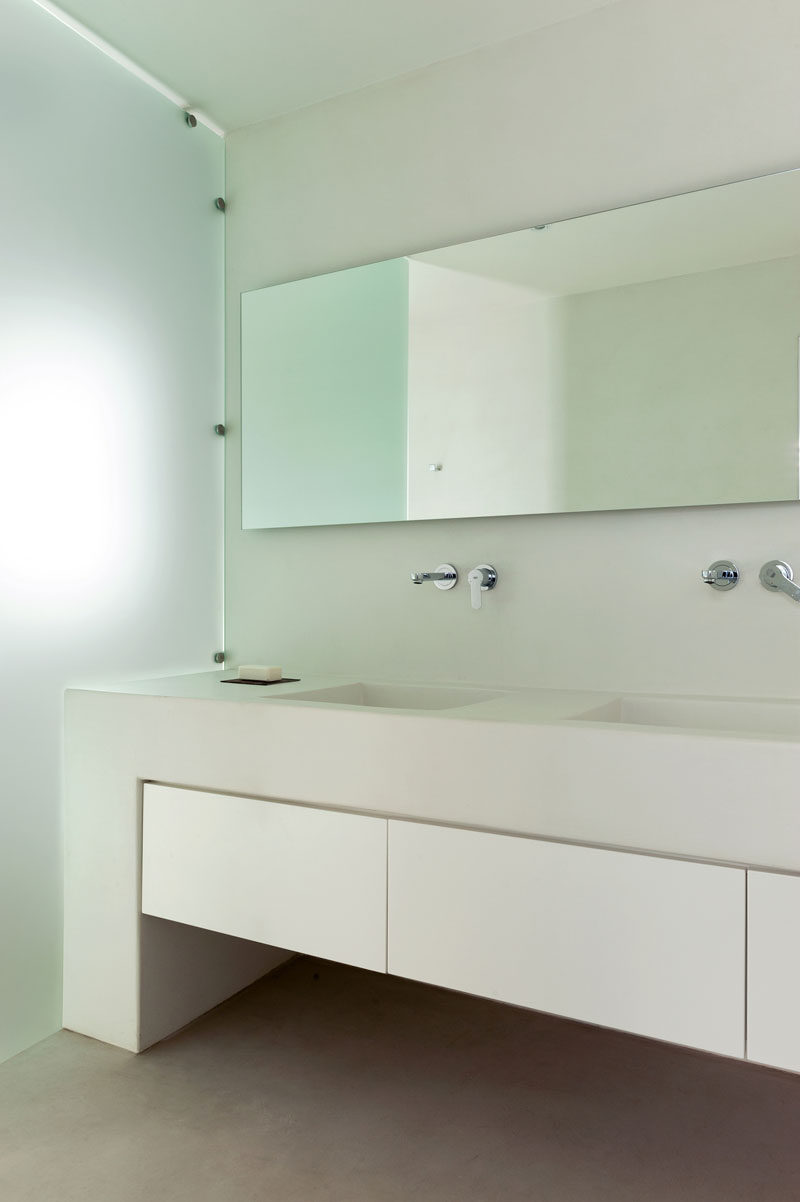 In this modern master bathroom, a large built-in vanity with storage provides plenty of space for dual sinks, while frosted glass acts as a shower screen. #ModernBathroom #Bathroom #Vanity