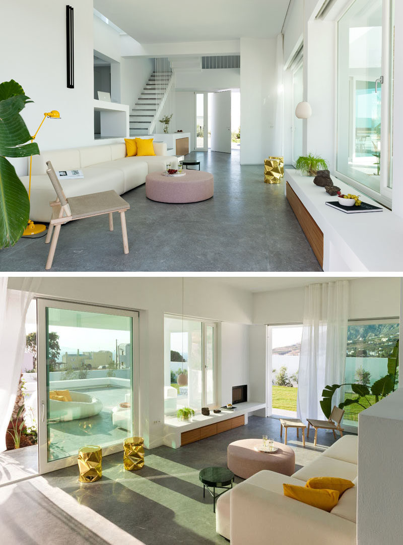Stepping inside this modern house, the interior with white plaster walls is just as bright as the exterior. The living room has pops of color and touches of wood, while grey cement plaster has been used for the floor. #WhiteInterior #ConcreteFloors #ModernInterior