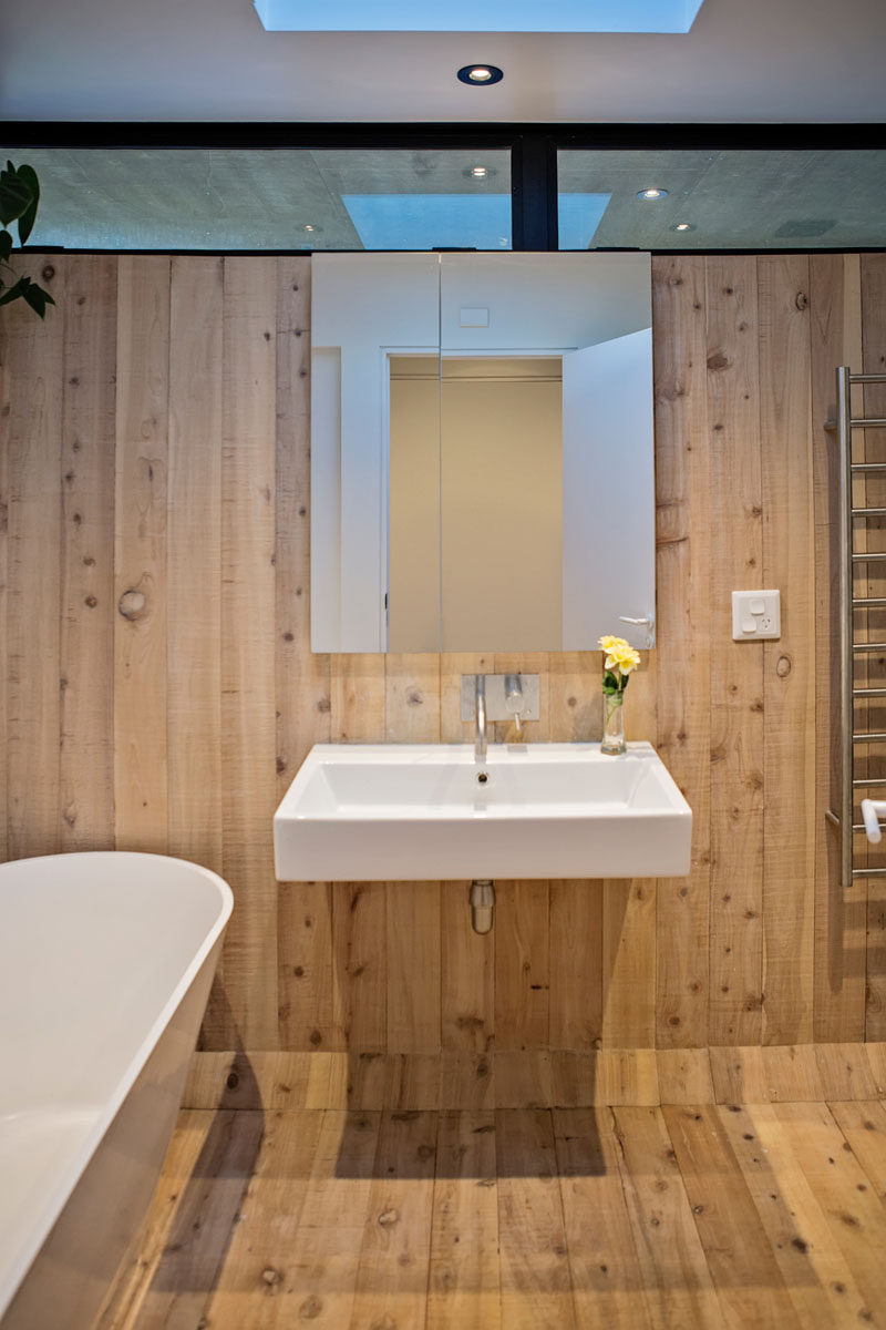 A simple color palette of wood and white has been used for the design of this modern bathroom, with a skylight adding natural light during the daytime. #ModernBathroom #Wood #WoodBathroom #Skylight