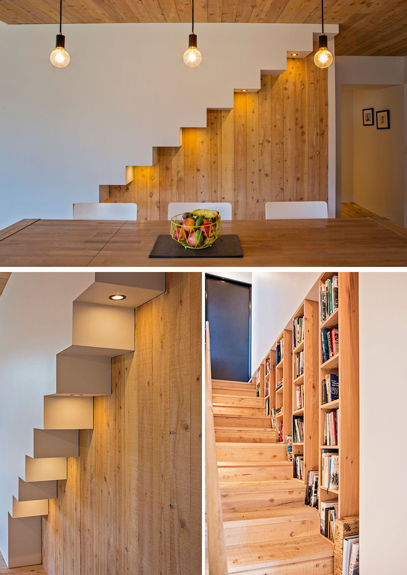 Beside the dining table in this modern house is an outline of the stairs that feature hidden lighting that highlights the design of the stairs. Wood bookshelves run alongside the stairs that lead up to the mezzanine. #Stairs #Lighting #InteriorDesign #Bookshelves #WoodInterior