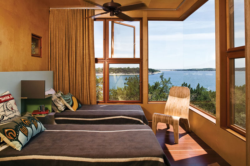 This modern bedroom has Birch plywood walls, while a large corner window reveals wide views of the woods and the lake. #CornerWindow #BirchWalls #PlywoodWalls #ModernBedroom #BedroomDesign
