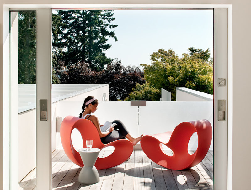 On the upper floor of this modern house there's a small outdoor space with curvaceous red chairs. #OutdoorSpace #Balcony