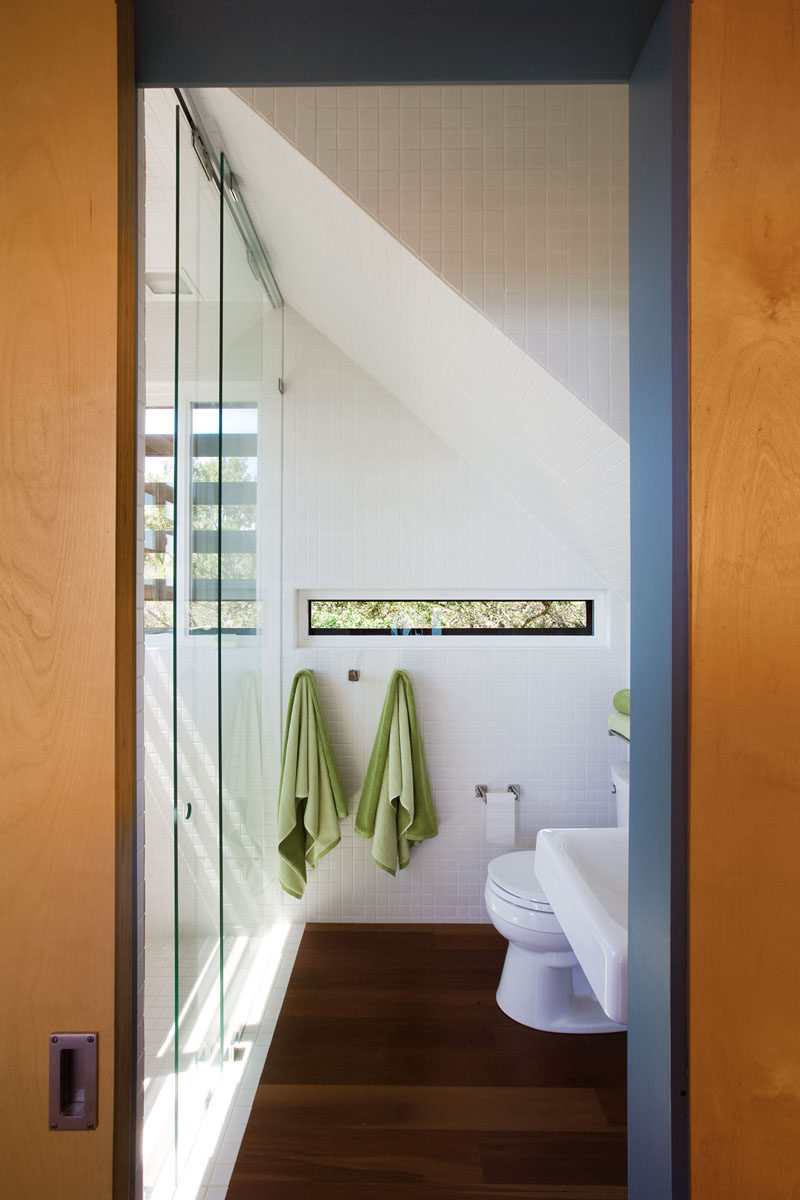 In this modern white and wood bathroom, small windows provide views and add natural light, however they are small enough to provide privacy at the same time. Floor-to-ceiling white tiles help to keep the interior bright. #ModernBathroom #WhiteBathroom #WoodFlooring #BathroomDesign