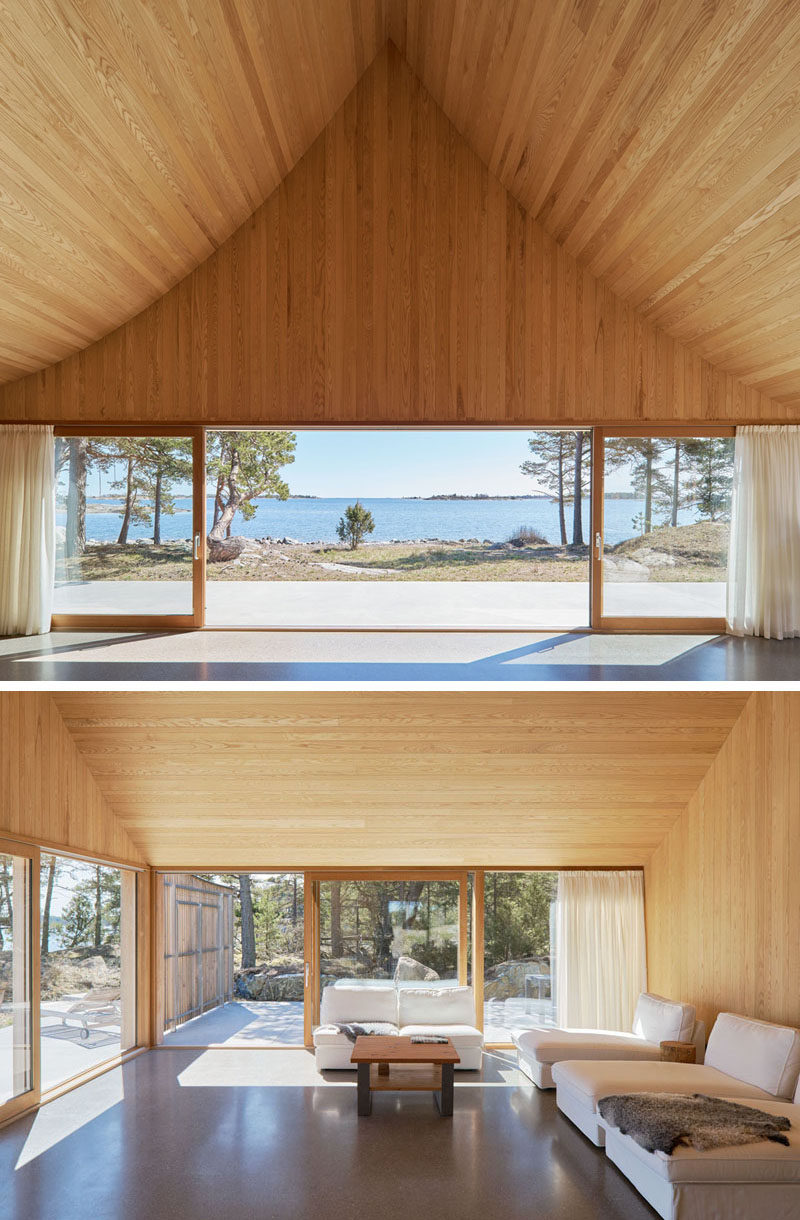 Cedar has been used to line the interior of this Scandinavian house, with the internal ridge of the ceiling measuring in at 18 feet (6m). In the living room, there's access to the front terrace as well as a side terrace for when it gets windy. #Architecture #Ceiling #InteriorDesign #LivingRoom #SlidingGlassDoors