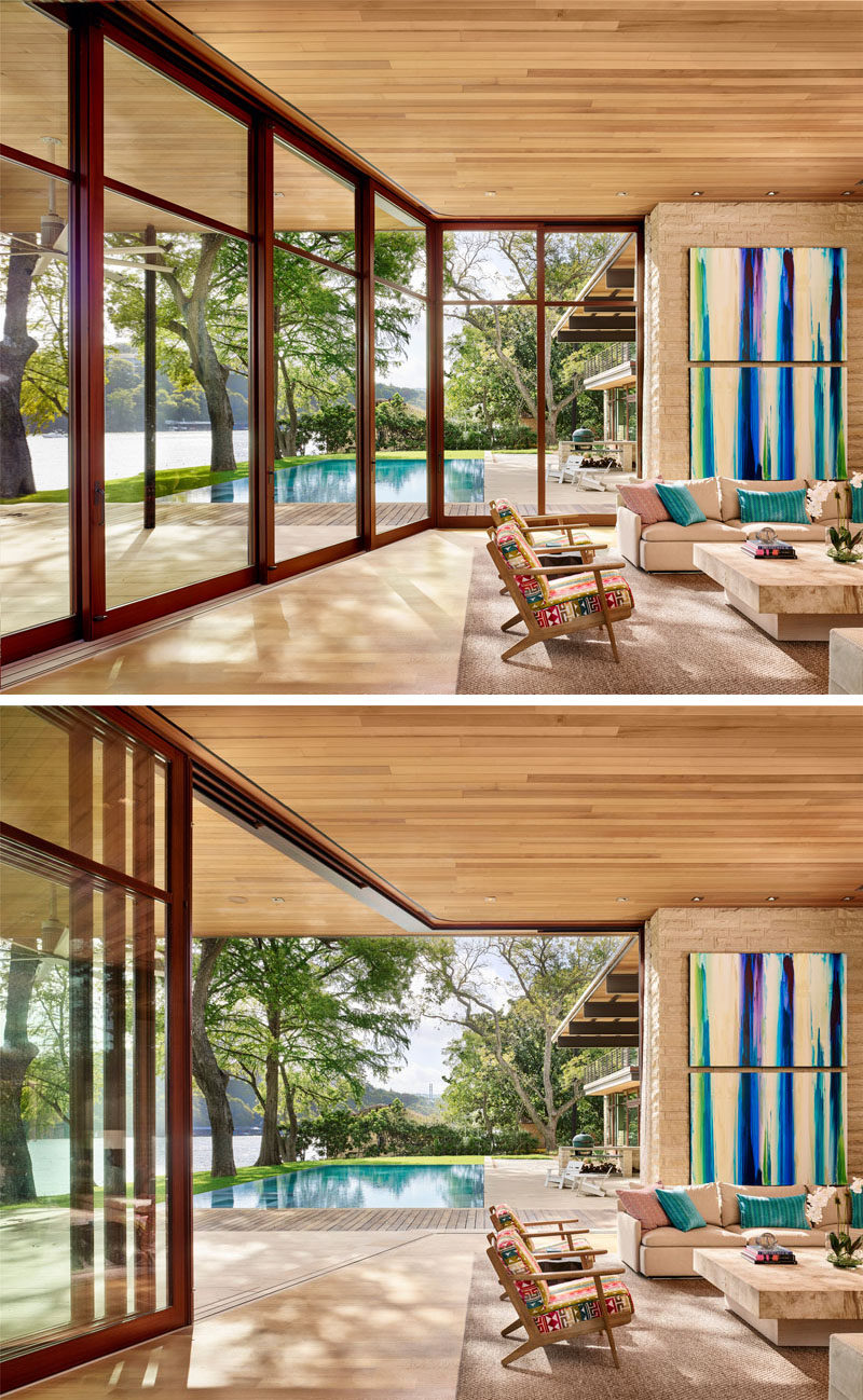This modern and casual living room has a bright pop of color in the form of artwork and large wood-framed sliding glass walls can be opened to connect the interior living spaces with the swimming pool and deck outside. #LivingRoom #GlassWalls #Windows #IndoorOutdoorLiving #InteriorDesign