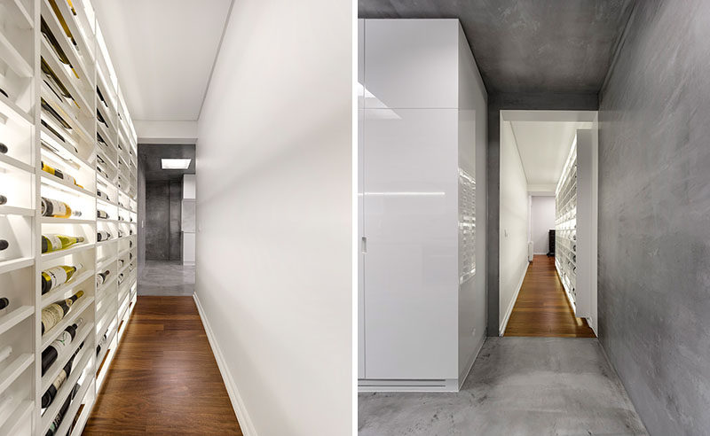This modern apartment has a backlit wine wall in a hallway that connects the entrance hall to the kitchen. #WineStorage #WineWall