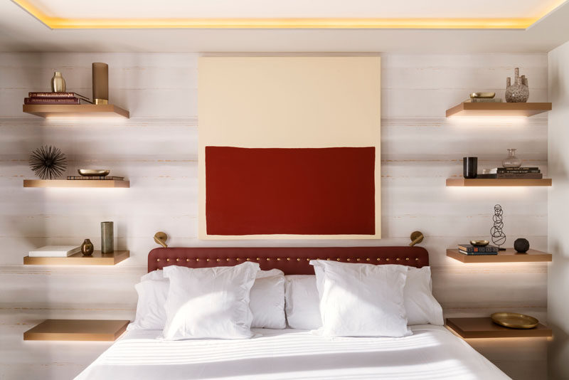 In this modern bedroom, four floating wood shelves with hidden lighting have been installed, with the lowest shelf at the correct height for a bedside table, while the other three shelves have been used to display decorative items. #BedroomDesign #BedsideTable #InteriorDesign #Shelving