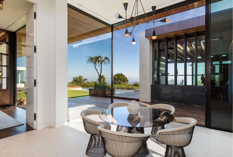 Large floor-to-ceiling windows in this contemporary dining room provide views of the backyard and add plenty of natural light to the space. #Windows #DiningRoom