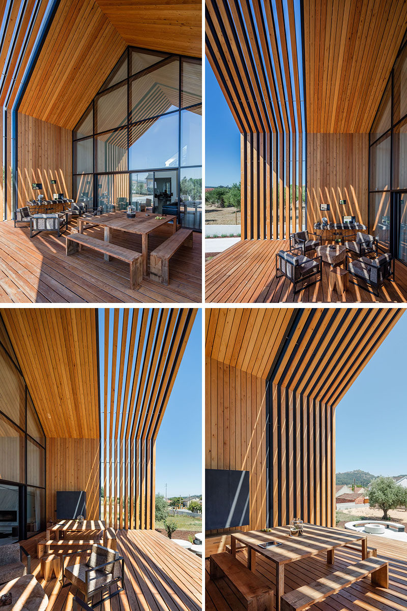 This modern house has a large wall of windows that provides access to a covered deck that's surrounded by wood. The deck has been set up as an outdoor dining and lounging area. #Deck #Architecture #ModernHouse #OutdoorDining