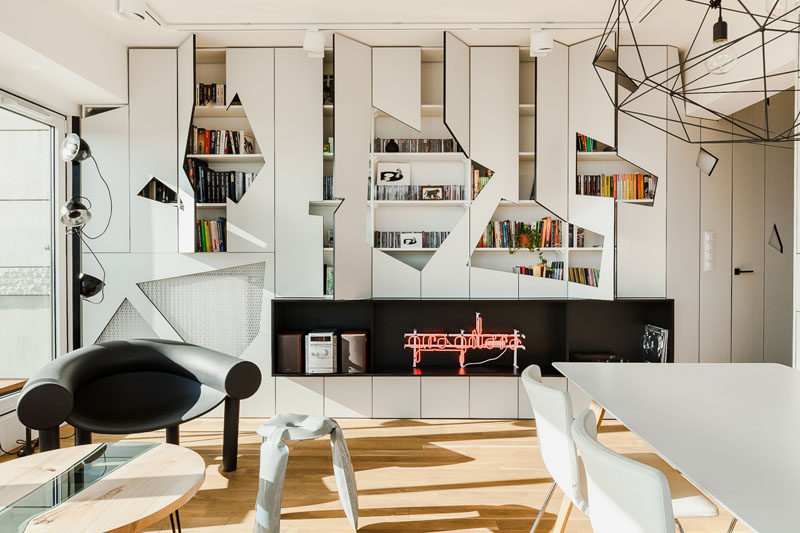 This modern apartment has a wall of white cabinets that have geometric cut-outs in the doors to add an artistic feature to the interior. #Cabinets #Geometric #LivingRoom #InteriorDesign #ModernLivingRoom