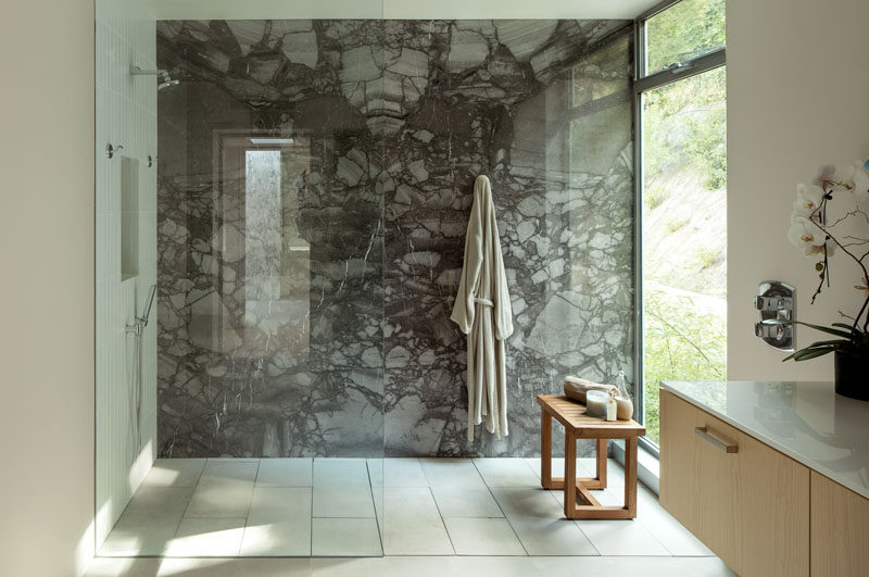 In this modern bathroom, a dark stone accent wall highlights the glass enclosed shower, while a large window provides ample natural light. #StoneWall #GlassEnclosedShower #ModernBathroom