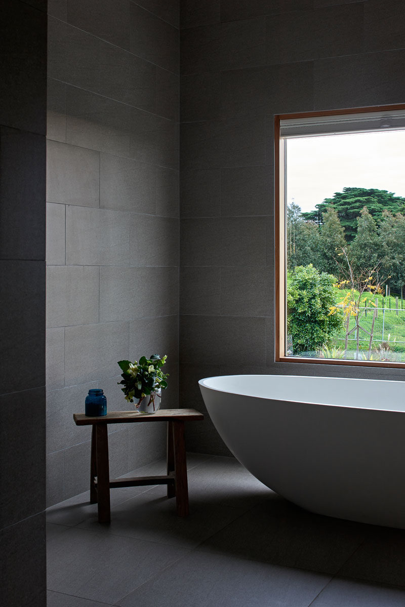 In this modern bathroom, large grey tiles have been paired with wood window frames and a white bathtub for a contemporary appearance. #GreyBathroom #GreyTiles #ModernBathroom #BathroomDesign