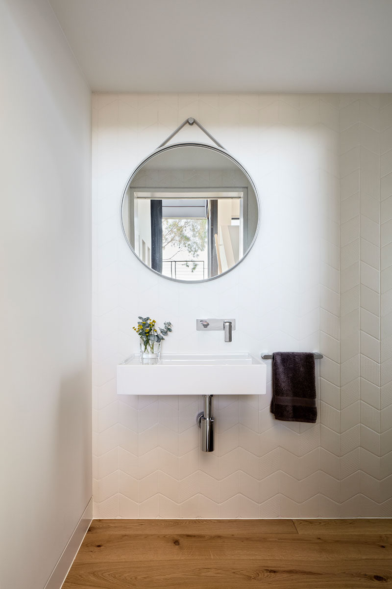 In this modern bathroom, a round mirror hangs on the wall, while white tiles in a chevron pattern cover the wall. #BathroomDesign #RoundMirror #ChevronTiles #WhiteTiles