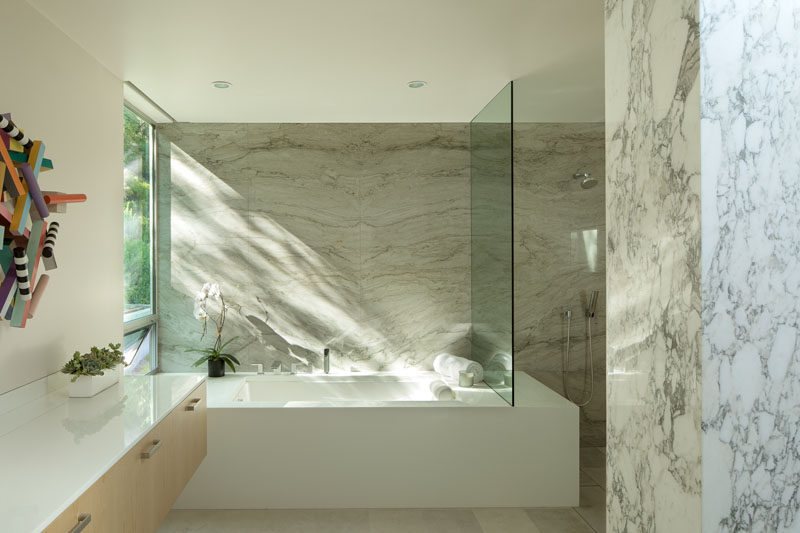 In this modern bathroom, a built-in bathtub has been positioned to take advantage of the tree views, and a glass partition separates the shower from the rest of the bathroom. #ModernBathroom #StoneWalls #BathroomDesign