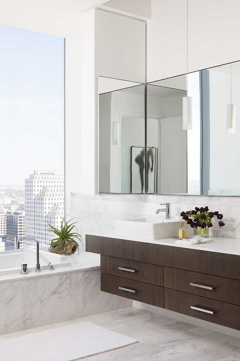 In this modern bathroom, high ceilings make the room feel larger than it is, and the bathtub has been positioned in front of the windows to take advantage of the views. #BathroomDesign #ModernBathroom #InteriorDesign