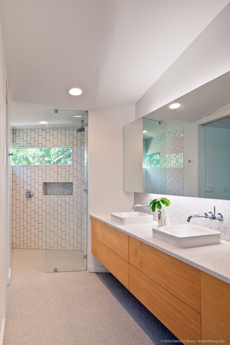 In this modern bathroom, there's a large double-sink vanity and a walk-in shower with a glass shower door and white tiles. #ModernBathroom #BathroomDesign