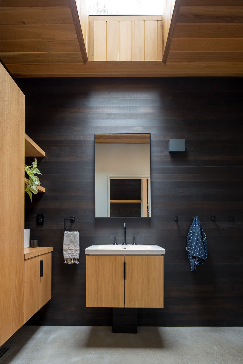 In this modern bathroom, dark wood has been used as an accent, while white oak cabinets, vanity and ceiling add a sense of warmth to the bathroom. #DarkWood #WhiteOak #ModernBathroom