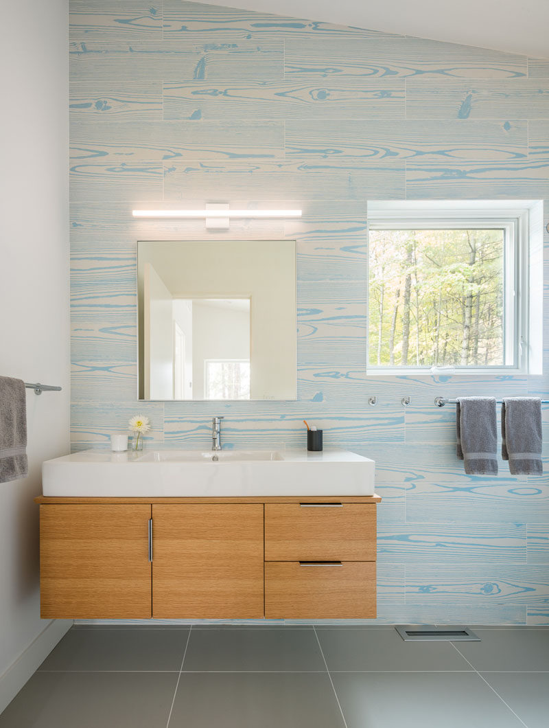 In this modern bathroom, wood grain tiles in a light blue create a unique and colorful accent wall. #ModernBathroom #AccentWall
