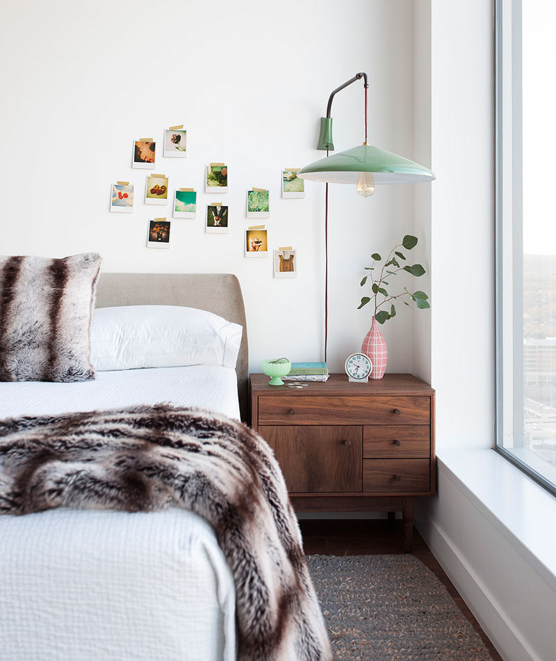 In this modern girl's bedroom, a pendant lamp attached to the wall hangs above a wood bedside table, while faux fur accents have been added to the bed. #BedroomDesign #ModernBedroom #InteriorDesign