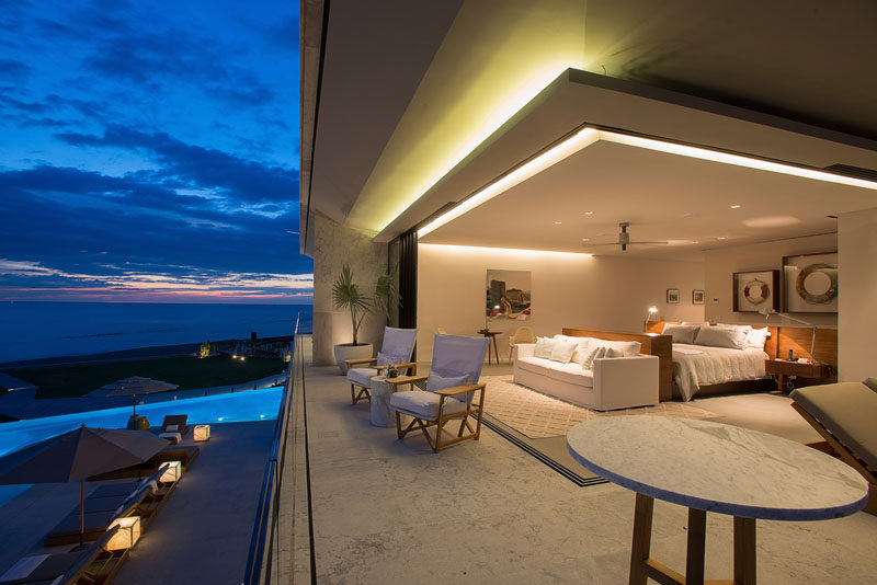 Sliding glass walls open up this modern bedroom to the balcony, and lighting is used to highlight the design elements of the home. #ModernBedroom #Architecture #Lighting