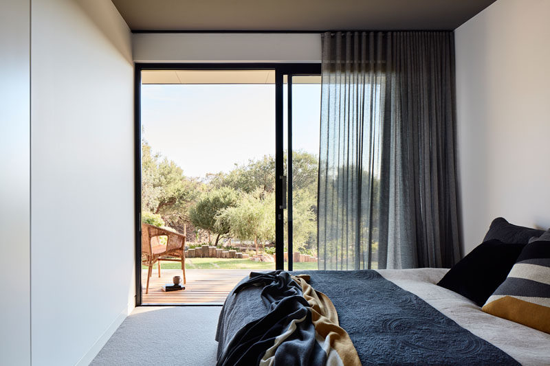 In this modern bedroom, a sliding glass door can be opened to have direct access to the backyard. #SlidingGlassDoor #Bedroom