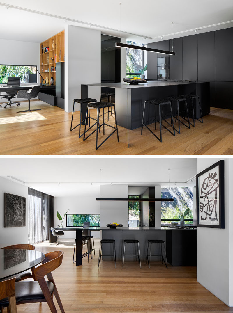 In this bold kitchen, matte black kitchen cabinets have been paired with a large black island with plenty of seating to create a modern appearance. #BlackKitchen #KitchenDesign #ModernKitchen