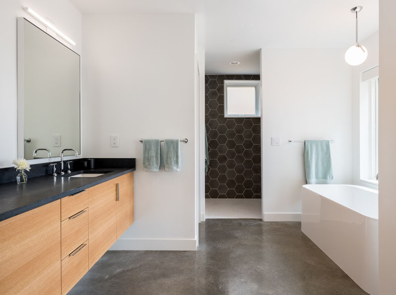 In this modern bathroom, white walls have been paired with dark grey hexagonal tiles, a concrete floor and a wood vanity with a dark countertop. #ModernBathroom #GreyTiles