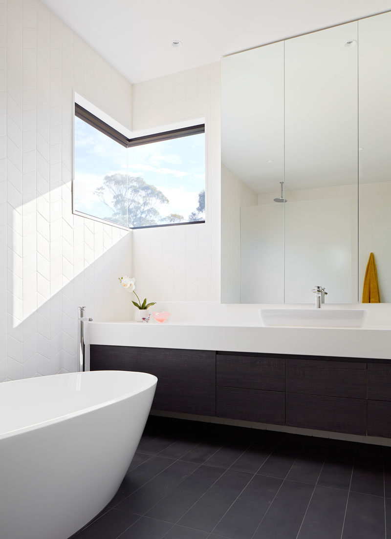 In this modern en-suite bathroom, a corner window adds natural light and provides a view of the trees, while dark flooring and a dark vanity contrast the white bathtub and white floor-to-ceiling tiles. #ModernBathroom #BathroomDesign #CornerWindow