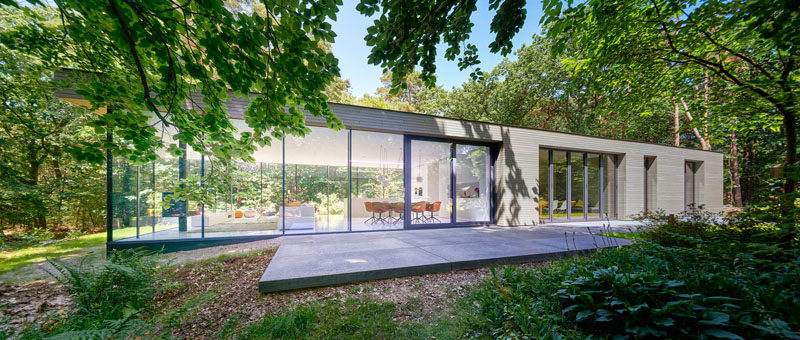 This modern villa has one end completely surrounded by glass that allows the living room to out onto the garden. #ModernHouse #HouseDesign #Architecture