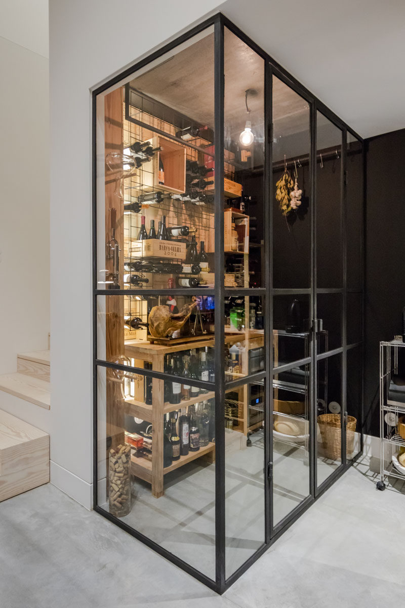 This black framed glass enclosed wine cellar has shelving and crates for wine storage. #WineCellar #WineStorage #WineRoom