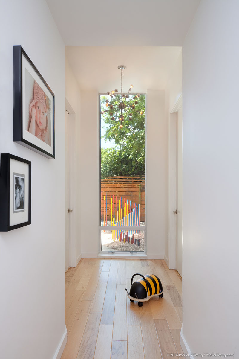 This small light-filled hallway provides access to the new bedrooms and gives a glimpse of the sculpture garden outside. #Hallway #Windows