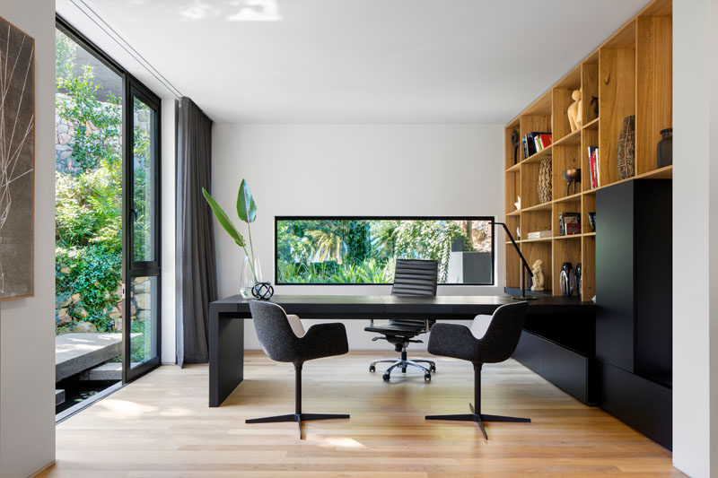 In this modern home office, built-in wood shelving lines the wall and the black cabinets match the black desk. #HomeOffice #ModernHomeOffice #WoodShelving
