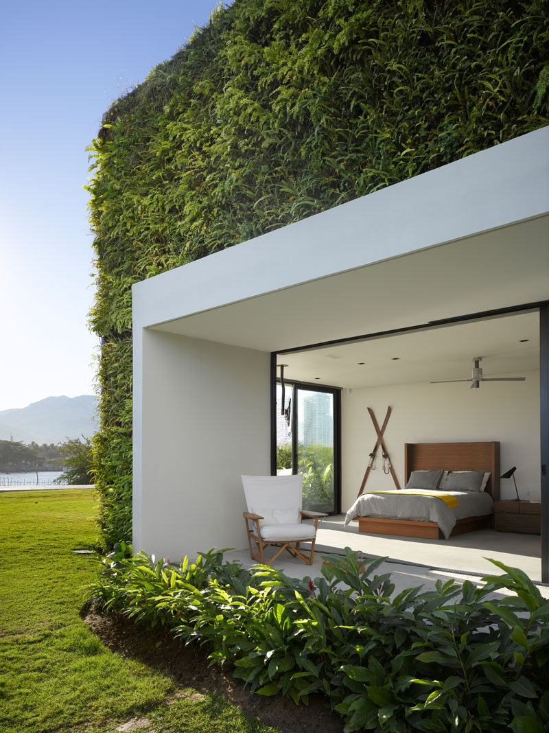 This modern bedroom has a covered outdoor space, while a green wall has been installed on the exterior of the house. #GreenWall #ModernBedroom #Architecture
