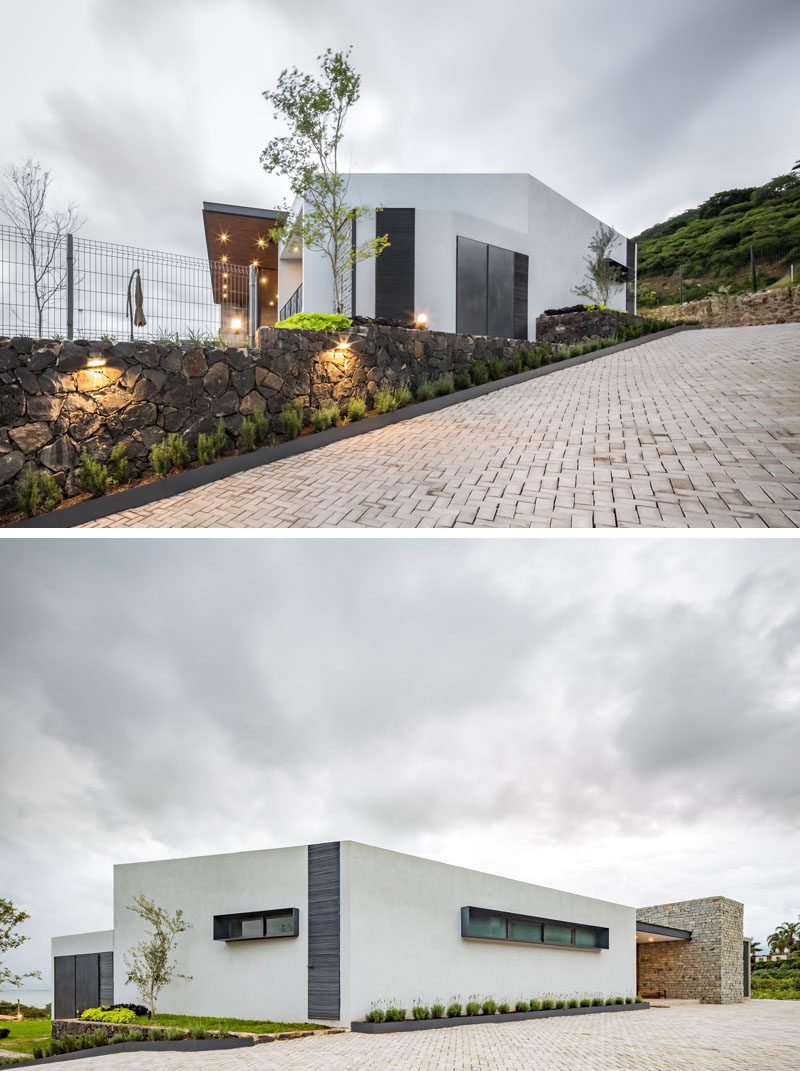 A stone wall with small plants runs alongside the driveway and leads up to the front door of this modern house. #Driveway #Landscaping #StoneWall #ModernHouse