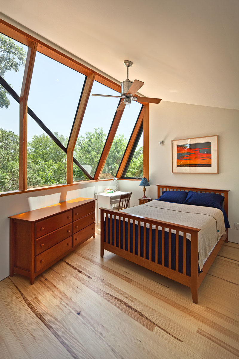 This master bedroom suite has large angled windows that look out to the old oak tree and provide views of the neighborhood. #Windows #Bedroom #AngledWindows