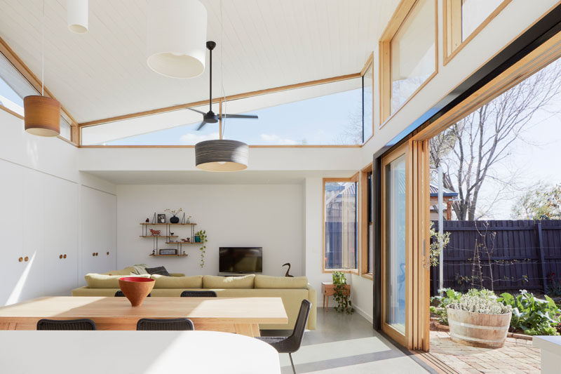 This sculptural roof sits over the extension and twists symmetrically around a central ridge. Clerestory windows follow the roof line allow sunlight to enter the interior from all sides. #ModernHouseExtension #Windows #Architecture