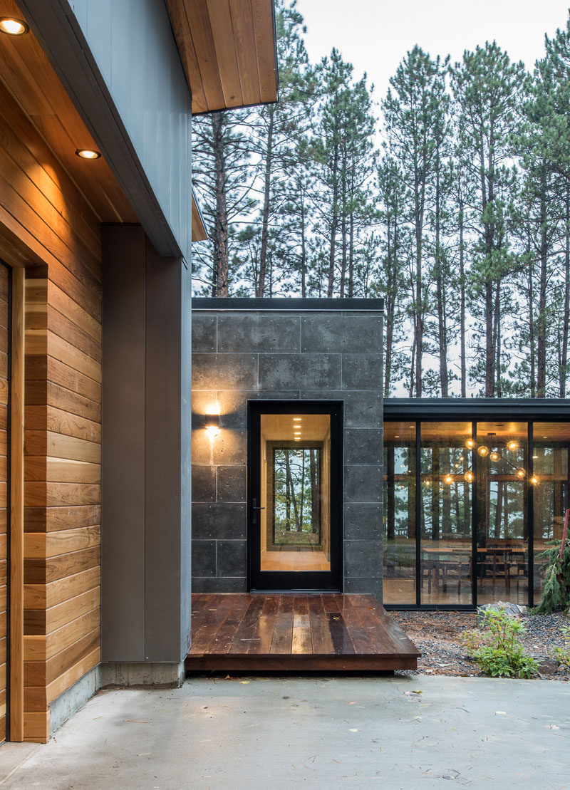 This modern house has a subtle dark exterior that includes grey, black, stone and wood elements, allowing the home to blend into the forested landscape. #ModernHouse #Wood #Grey #Stone