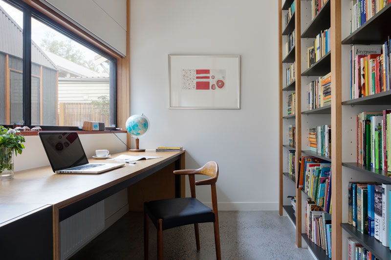 This home office has a wall full of shelving for books and a window that looks out onto a courtyard. #HomeOffice #Study #Bookcase #Shelving