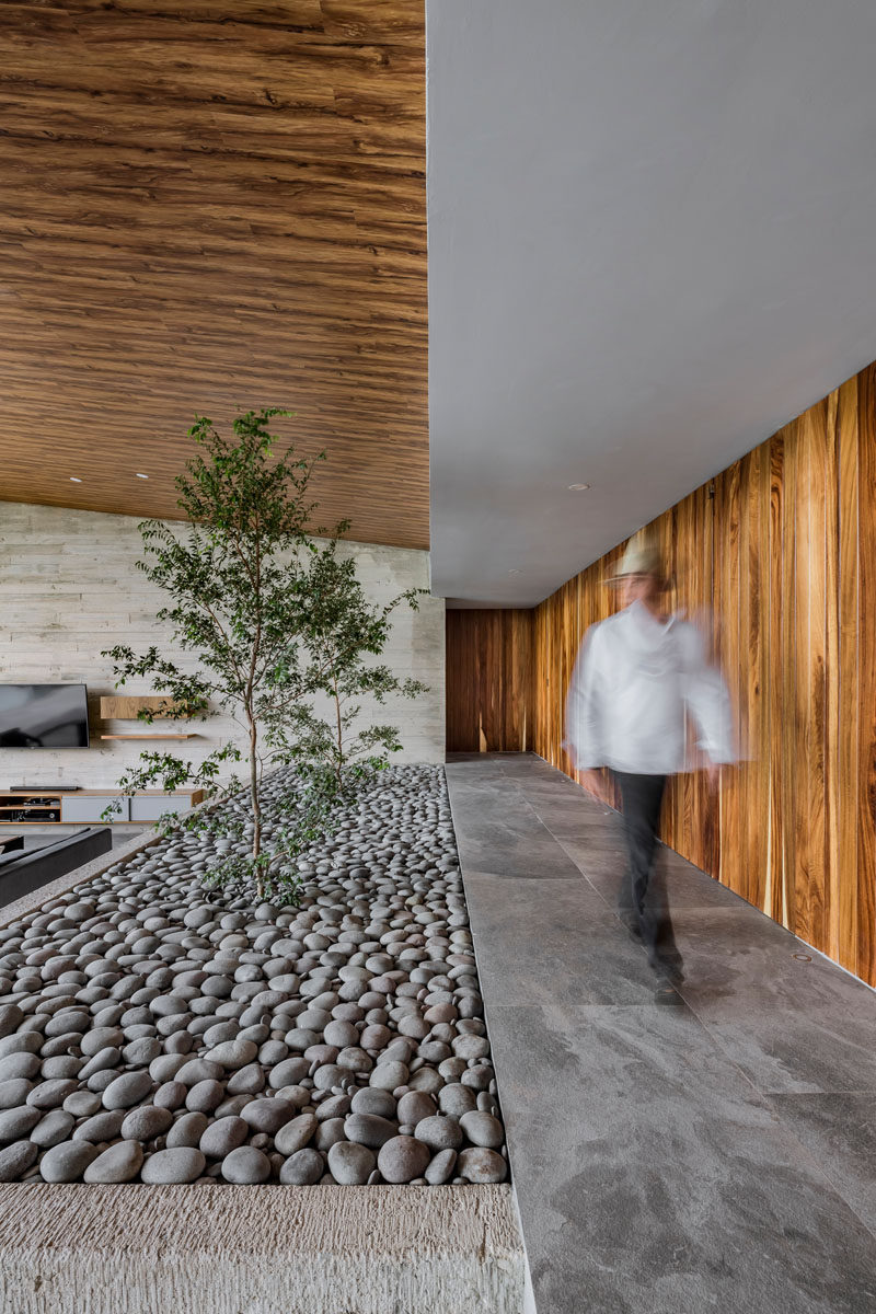 This modern house has a raised walkway that leads to the bedrooms and bathrooms. A small stone covered indoor garden adds a touch of nature to the interior. #IndoorGarden #Stone #InteriorDesign #ModernHouse