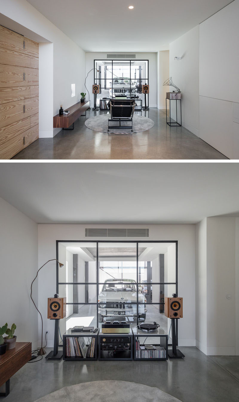 This modern house has a music room, which is set up with a record player and a relaxing lounge chair look out through a black-framed glass wall that provides a view into the garage. #MusicRoom #InteriorDesign #GlassWall