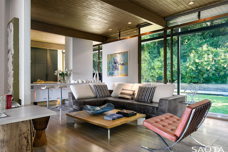 This modern house has a sitting area next to the kitchen and it opens up to the backyard. #SittingArea #LivingRoom #WoodCeiling