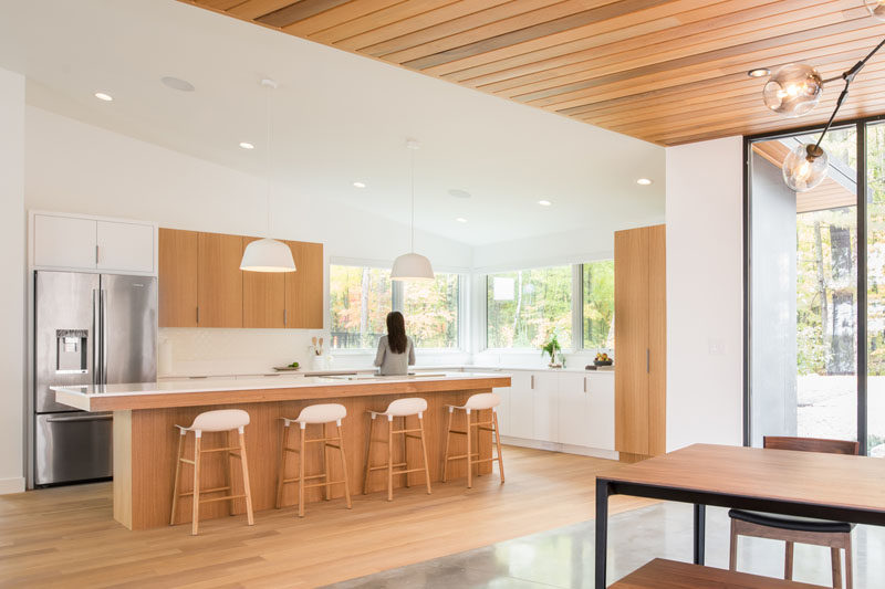 In this modern kitchen, bright white walls are warmed up with the use of white oak cabinets, and large windows let the surrounding tree views become the highlight of the kitchen. #ModernKitchen #KitchenDesign